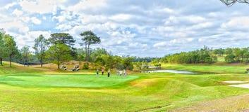 打高尔夫球的家庭在谷下 库存照片