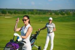 打高尔夫球的少妇和人 免版税图库摄影