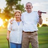 打高尔夫球的愉快的资深夫妇画象享受退休 免版税库存图片