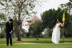 打高尔夫球的新娘和新郎 免版税库存照片