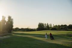 打高尔夫球的高尔夫球运动员和球童 库存图片