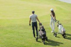 打高尔夫球的年轻夫妇 库存照片