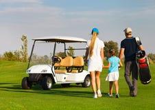打高尔夫球的年轻嬉戏家庭 免版税库存照片