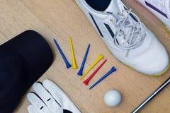 打高尔夫球象鞋子、发球区域、手套、球和盖帽的工具 免版税库存照片
