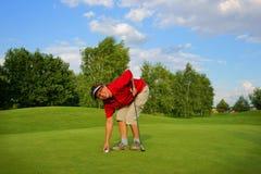 打高尔夫球,去掉从孔的女子高尔夫球运动员一个球 免版税库存图片