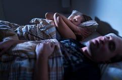 打鼾在晚上 睡眠停吸 盖耳朵的沮丧的懊恼失眠的妇女用枕头在床上 停留的妻子醒 免版税库存图片