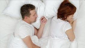 打鼾的人堵塞大声醒来的他的妻子在喧闹的夜期间和她关闭有枕头的耳朵 在视图之上 影视素材