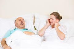 打鼾的人,生气妇女覆盖物耳朵,伪善言辞睡眠 免版税库存照片