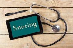 打鼾-医生的工作场所 片剂,医疗听诊器,在木书桌背景的黑笔 顶视图 库存照片