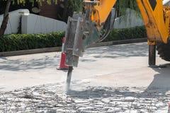 打破和操练修理的挖掘机混凝土路 免版税库存图片