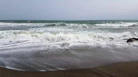 打破在一个多岩石的海滩的波浪 股票录像