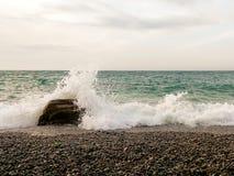 打破在一个石海滩的波浪,形成一朵大浪花 库存图片