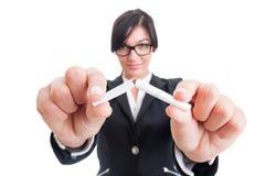 打破在一半的女商人一根香烟 免版税库存照片