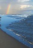 打破在与一条部份彩虹的岸的波浪 免版税库存照片