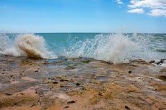 打破在岩石的波浪 库存照片