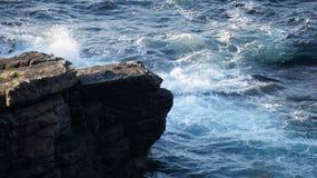 打破在峭壁的基地的波浪在Banba的冠,马林的 免版税库存照片