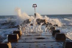 打破在海洋防御的波浪在伯恩茅斯在多西特靠岸在一个冬天晚上 免版税库存照片