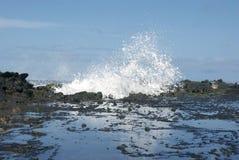 打破在熔岩岩石的波浪 免版税库存图片