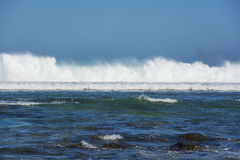 打破在珊瑚障碍的波浪在一个热带海滩旁边 免版税库存照片