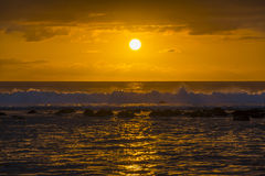 打破在珊瑚障碍的波浪在日落 免版税库存图片