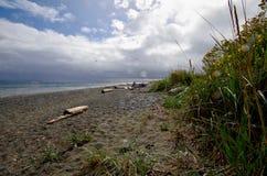 打破在雨急风期间的太阳在海滩 库存照片