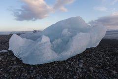 打破在黑岩石沙子海滩的秀丽冰 免版税库存照片
