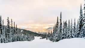 打破在滑雪小山的云彩的太阳 图库摄影