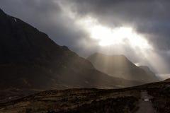 打破在Glencoe山的云彩的光束 库存照片