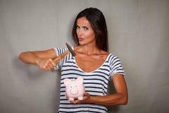 打破存钱罐的性感的深色的妇女 免版税库存图片