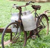 打破的送牛奶者的生锈的老自行车有两个老牛奶罐头的和 免版税库存照片