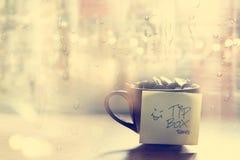 打翻箱子,在咖啡杯的硬币在咖啡馆前面镜子和雨水下落,葡萄酒颜色和软 免版税库存图片