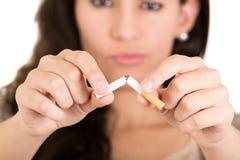 打破香烟的妇女。概念中止抽烟 免版税库存照片