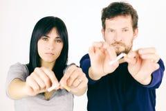 打破香烟的男人和妇女放弃烟 免版税库存照片