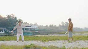 打tai池氏轻快优雅球的活跃资深夫妇在慢动作的海滩 股票录像