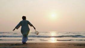 打tai池氏轻快优雅球的活跃资深夫妇在慢动作的海滩 股票视频