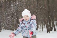 扔冬天的笑的小女孩下雪用她的手 图库摄影