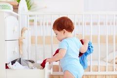 扔出去滑稽的婴儿的婴孩从梳妆台在家穿衣 免版税库存图片