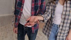 扔和捉住钥匙的一对愉快的夫妇的特写镜头对他们新的公寓 影视素材