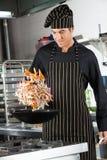 扔在铁锅的厨师混乱油炸物 免版税库存图片
