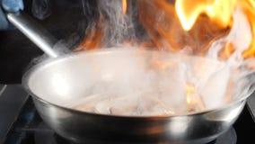 扔热的不粘锅的煎锅用海鲜,然后设置它在火的无法认出的厨师烹调flambe盘 ? 股票录像