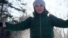 扔蓬松雪的年轻快乐的妇女在公园 股票视频