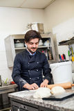 扔面团的厨师,当做酥皮点心时 免版税库存照片