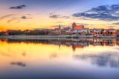 托伦老镇在维斯瓦河反射了在日落 库存图片