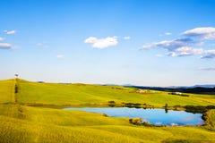 托斯卡纳、湖、树和绿色领域,在日落的农村风景, 免版税库存照片
