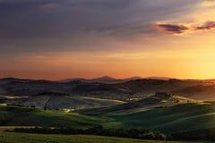 托斯卡纳春天,日落的绵延山 沃尔泰拉农村大局 库存图片