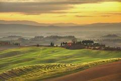 托斯卡纳春天,有薄雾的日落的绵延山 农村的横向 免版税库存图片