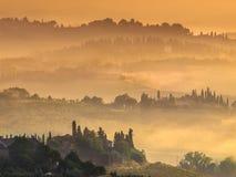 托斯卡纳村庄风景在一个有薄雾的早晨在8月 图库摄影