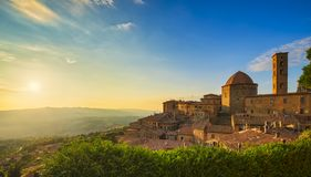 托斯卡纳,沃尔泰拉镇在日落的地平线、教会和全景视图 意大利 免版税库存照片