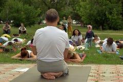 托木斯克俄罗斯- 2016年6月19日: :城市的居民在瑜伽的开放教训参与在中央公园 免版税图库摄影