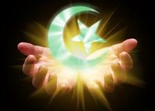 托起和拿着或者显示伊斯兰教的新月形月亮和星的手 免版税图库摄影